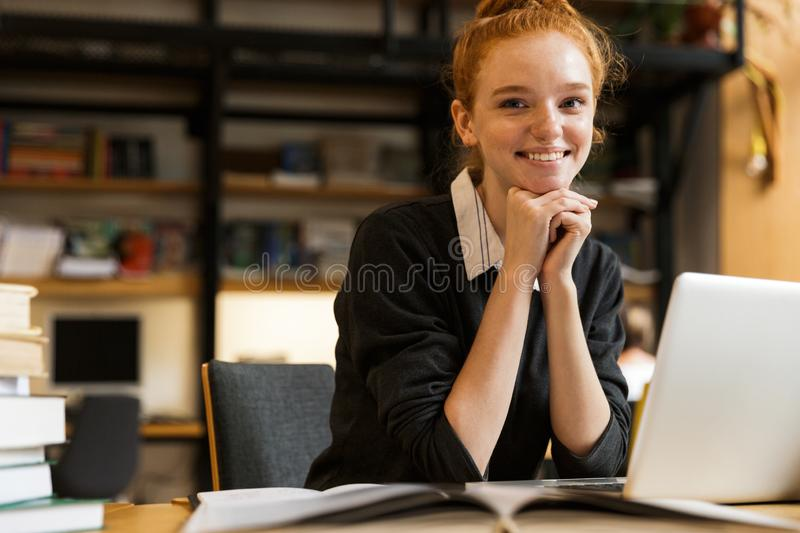 Smiling red haired teenage girl using laptop royalty free stock photo