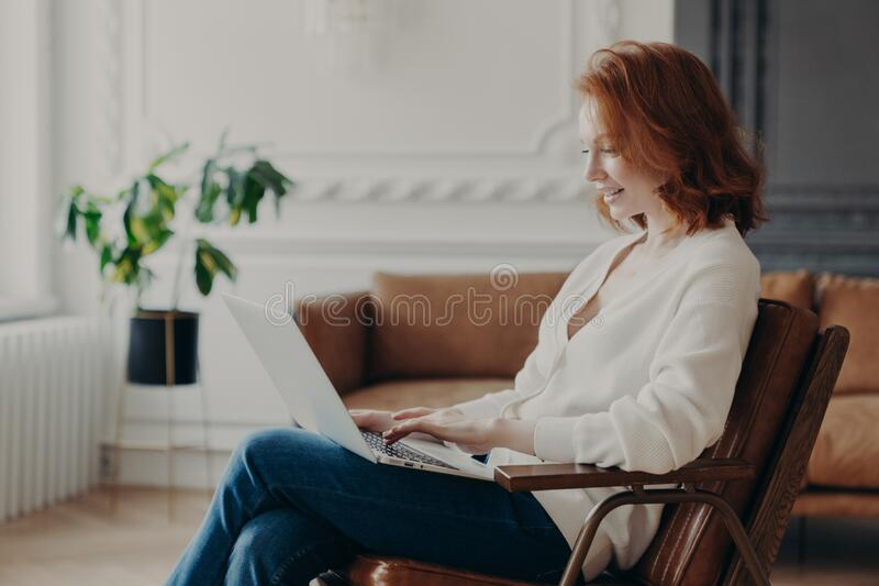 Smiling red haired woman freelancer sits in armchair, keyboards on laptop computer, uploads necessary material for developing site. Poses in modern apartment stock photos