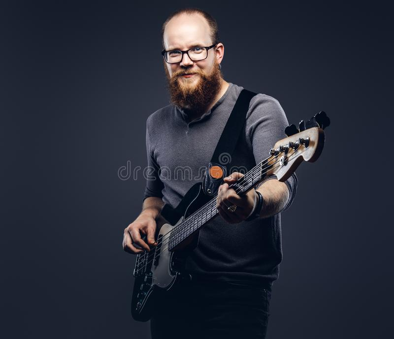 Smiling redhead bearded male musician wearing glasses dressed in a gray t-shirt playing on electric guitar. Isolated on. A gray background royalty free stock photos