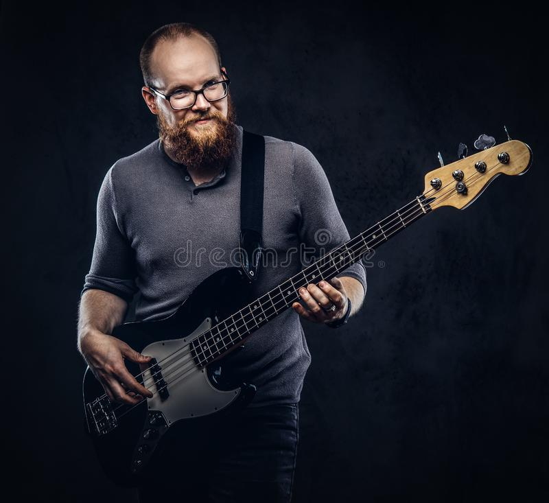 Smiling redhead bearded male musician wearing glasses dressed in a gray t-shirt playing on electric guitar. on. A dark textured background stock images