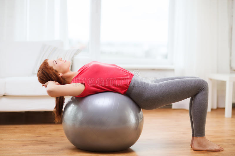 Smiling redhead girl exercising with fitness ball royalty free stock image