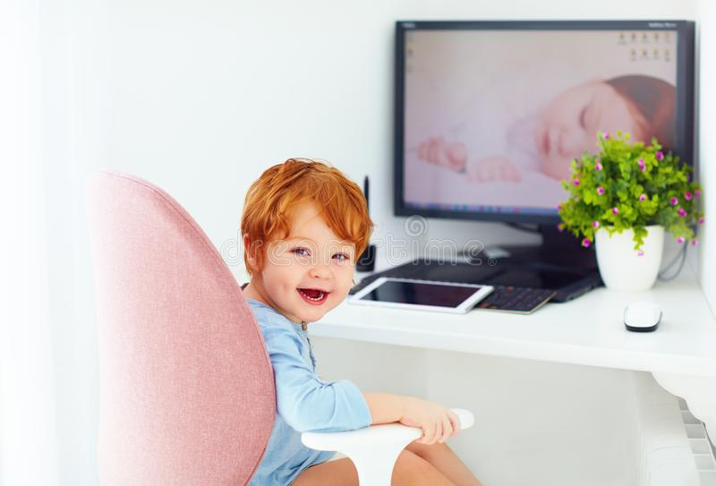 Happy redhead toddler baby boy is sitting in office chair at working place. Smiling redhead toddler baby boy is sitting in office chair at working place stock photography