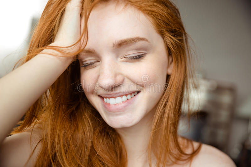 Smiling redhead woman with closed eyes stock photography