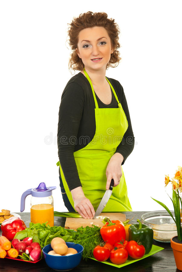 Smiling redhead woman cutting green onion stock photo