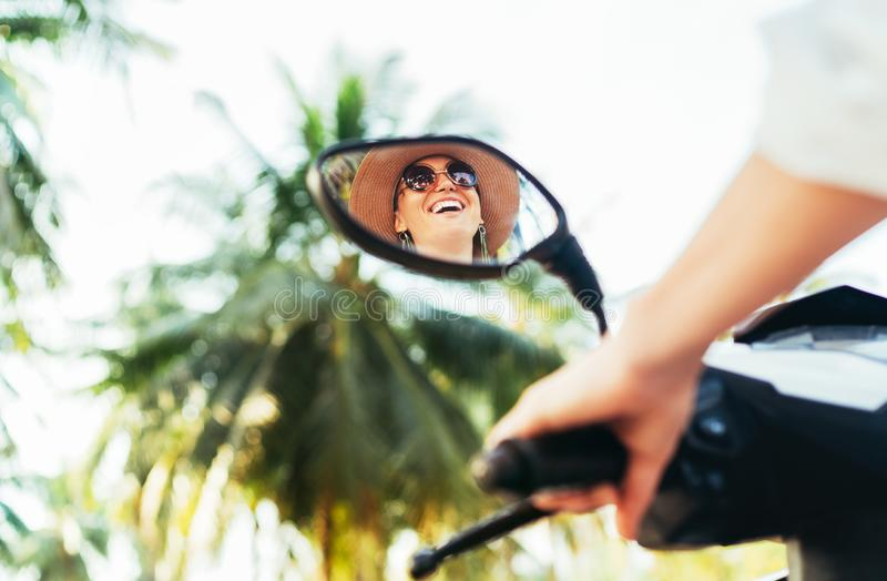 Woman riding motorbike mirrored in rear view mirror. Cheerful people during vacation time concept image royalty free stock images