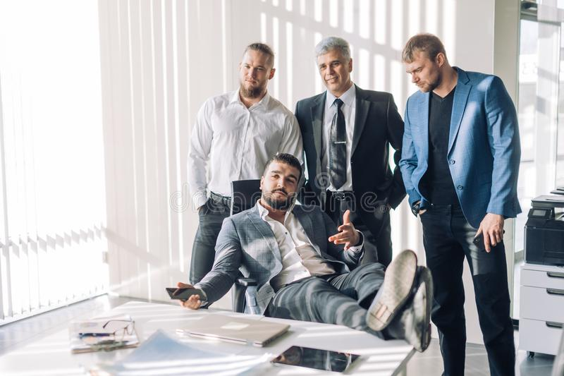 Optimistic businessman in white shirt collaborating with his team at meeting. Smiling relaxed boss in suit sitting at his office table looking at camera with royalty free stock image