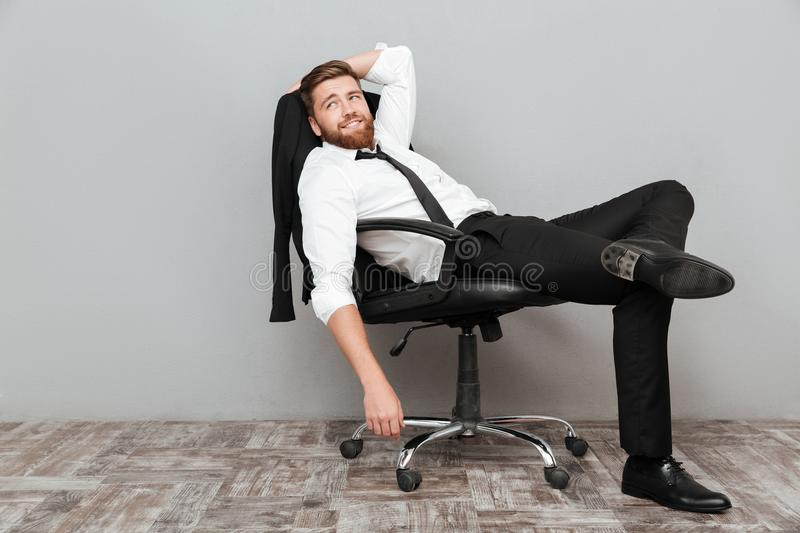 Smiling relaxed businessman resting in office chair. Over gray background stock photo