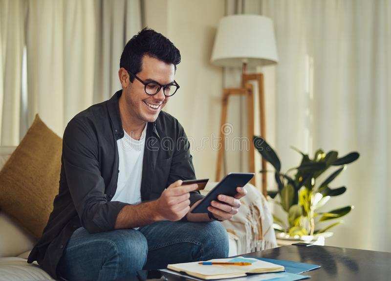 Cheerful man sitting in living room shopping online using credit. Smiling relaxed man sitting on sofa shopping online using smartphone and credit card at home royalty free stock photos