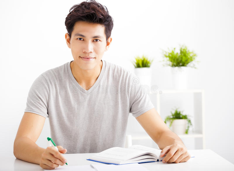 Smiling relaxed young man reading book royalty free stock image