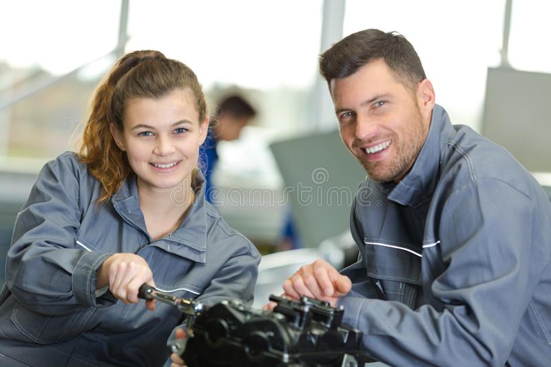 Smiling repairman and apprentice in auto mechanic royalty free stock photos