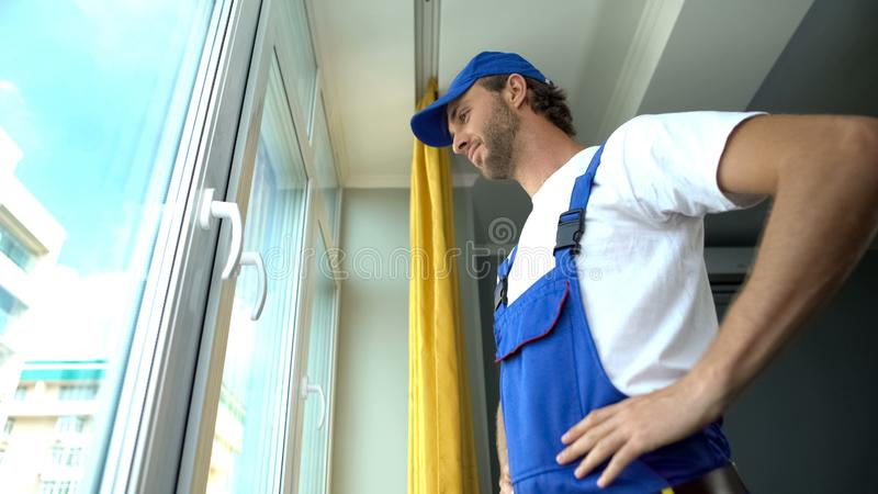 Smiling repairman satisfied with window system installation, quality service royalty free stock photo