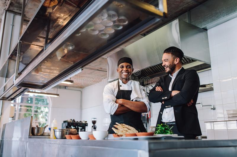 Smiling restaurant owner and chef standing in kitchen. Businessman with professional cook standing together and laughing royalty free stock photo