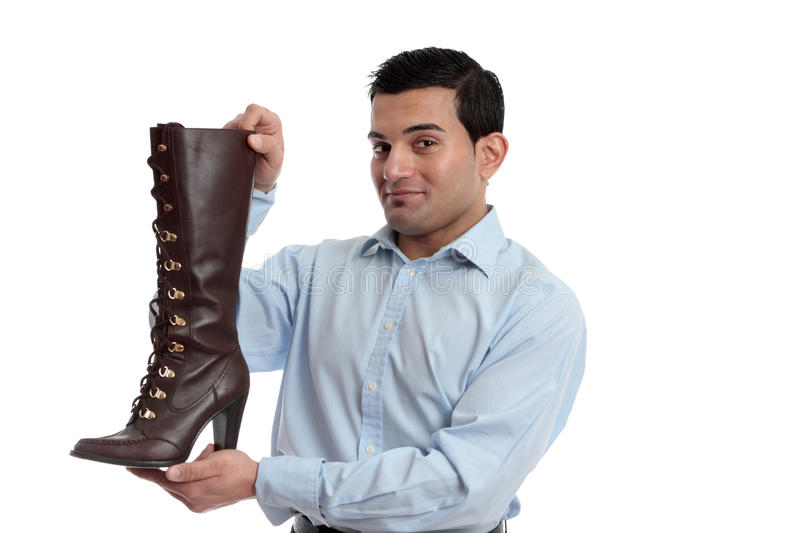 Smiling retail salesman. Holding or showing off a ladies leather boot stock images