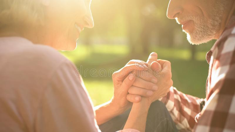 Smiling retired couple relaxing in park, holding hands and talking about love stock photos
