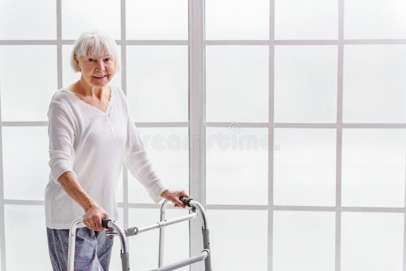 Smiling retiree holding gutter frame in hand stock images