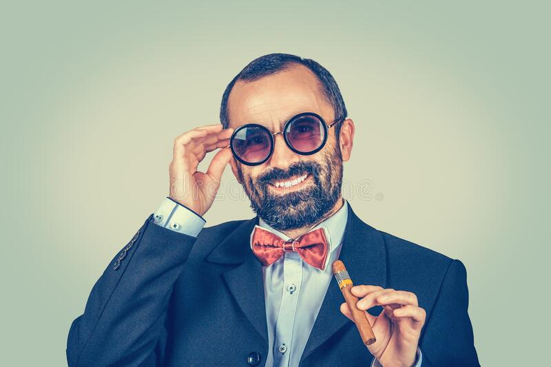 Smiling, rich, bearded man keeping round sunglasses and cuban cigar. Portrait of stylish, funny guy looking you camera. stock image