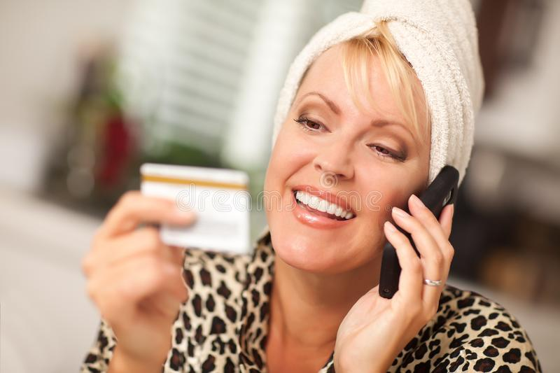 Smiling Robed Woman on Cell Phone With Credit Card