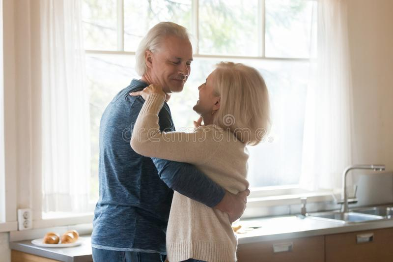 Smiling romantic aged couple dancing in kitchen stock images