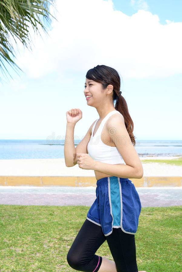 Smiling running woman. Young woman jogging by the sea stock photos