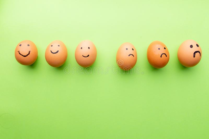 Smiling and sad eggs on a green background stock photo