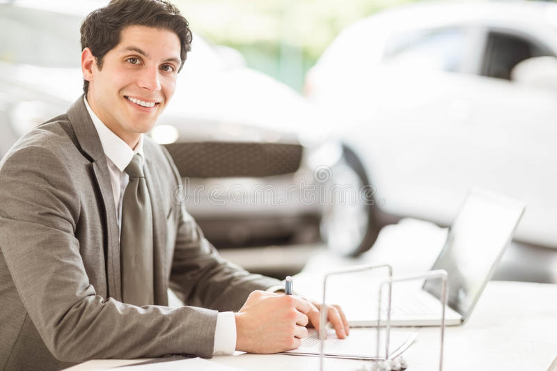 Smiling salesman at his desk stock images