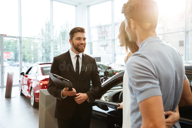 Smiling salesman showing new car to a couple royalty free stock photography