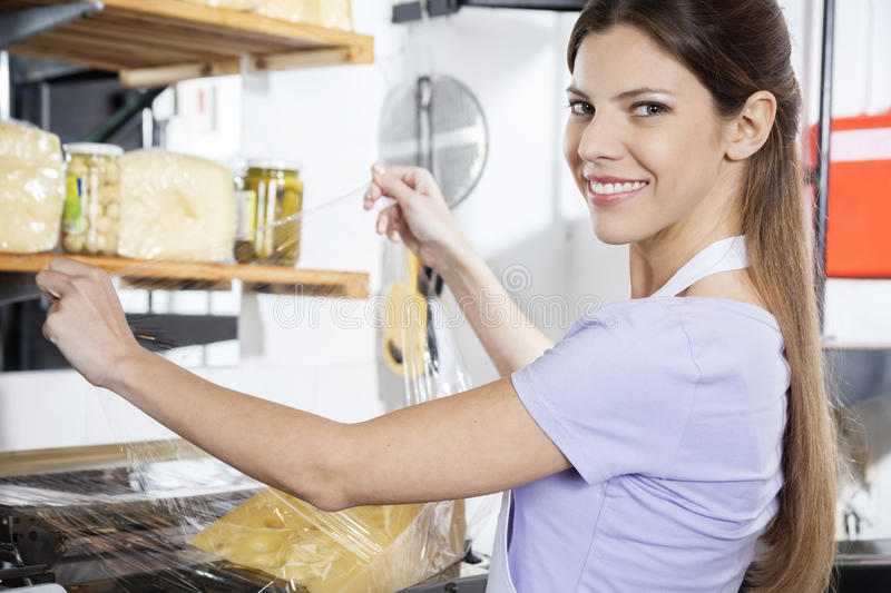 Smiling Saleswoman Packing Cheese At Grocery Store stock image