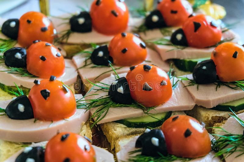 Smiling sandwiches with edible ladybugs from tomatos and olives, as well as bread, cheese, cucumber, sausage, dill stock image