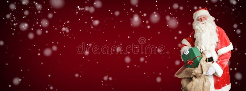 Smiling Santa Claus brings gifts in his big brown bag stock photography