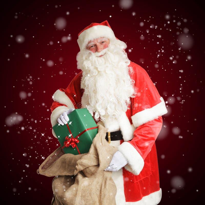 Smiling Santa Claus brings gifts in his big brown bag stock photo