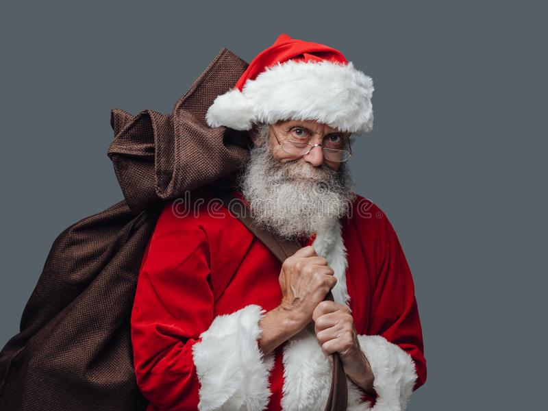 Santa Claus carrying Christmas gifts. Smiling Santa Claus carrying a sack with gifts on Christmas Eve royalty free stock photography