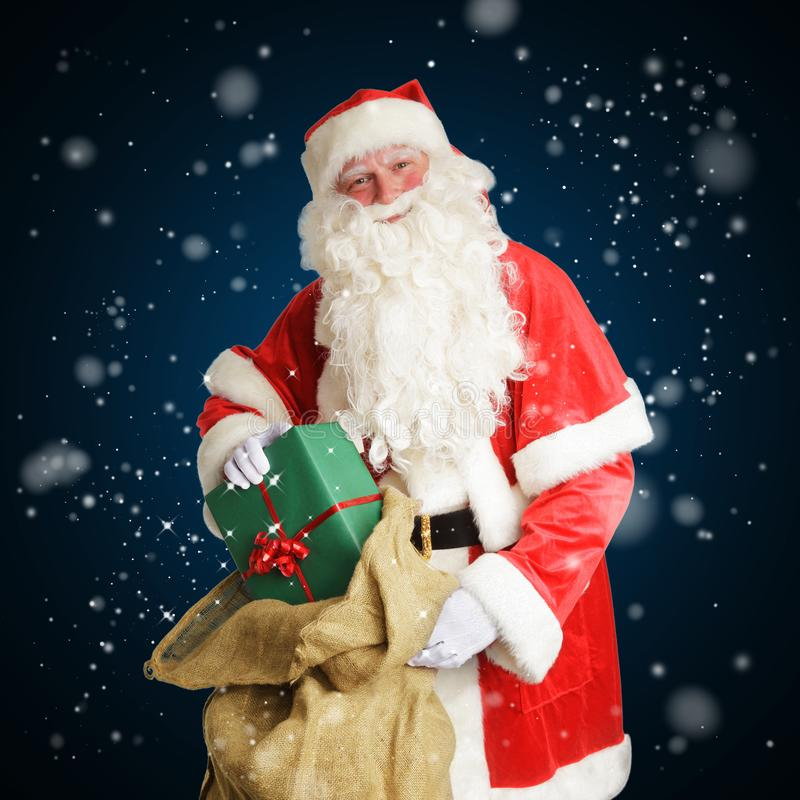 Smiling Santa Claus delivers gifts in a big brown bag royalty free stock image
