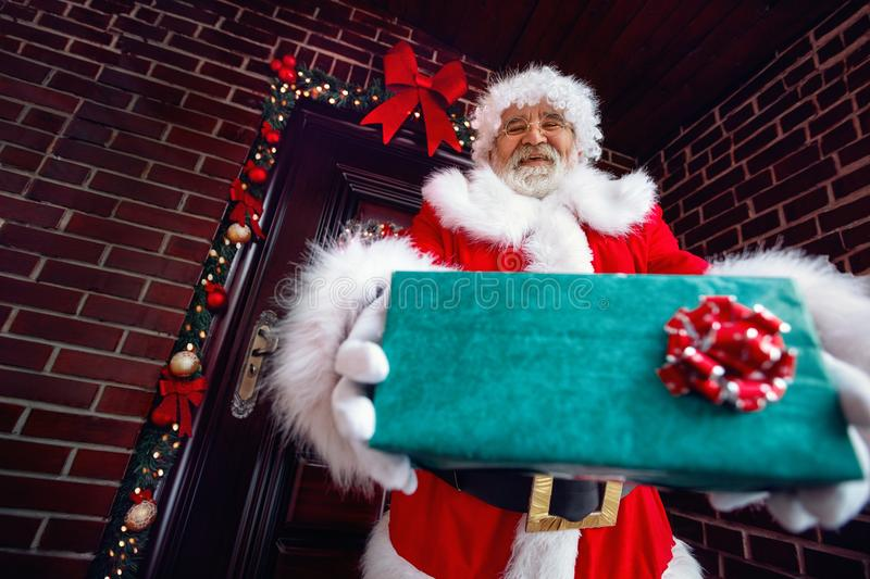 Smiling Santa Claus giving a Christmas present stock photos