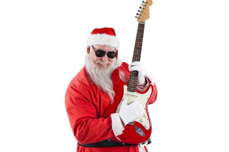 Smiling santa claus playing a guitar royalty free stock photography