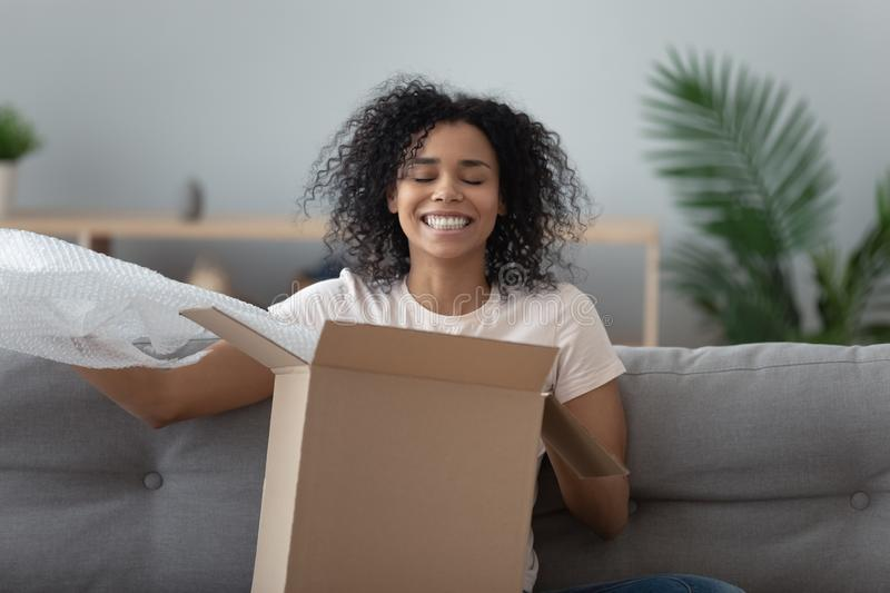 Smiling satisfied African American woman client unboxing parcel royalty free stock images