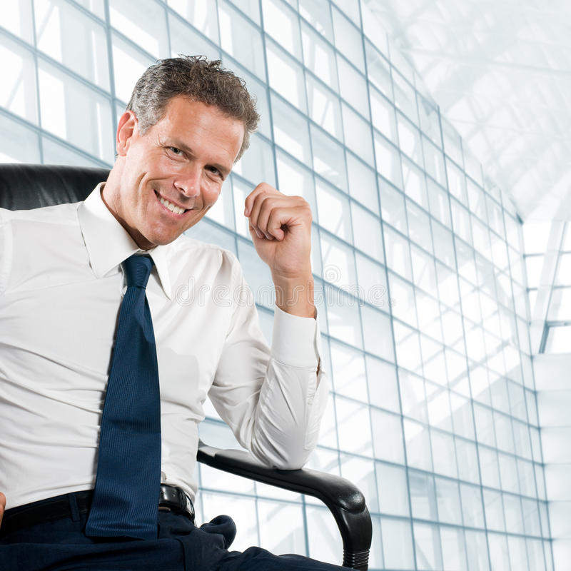 Smiling satisfied businessman. Looking at camera sit in his chair at office royalty free stock photography