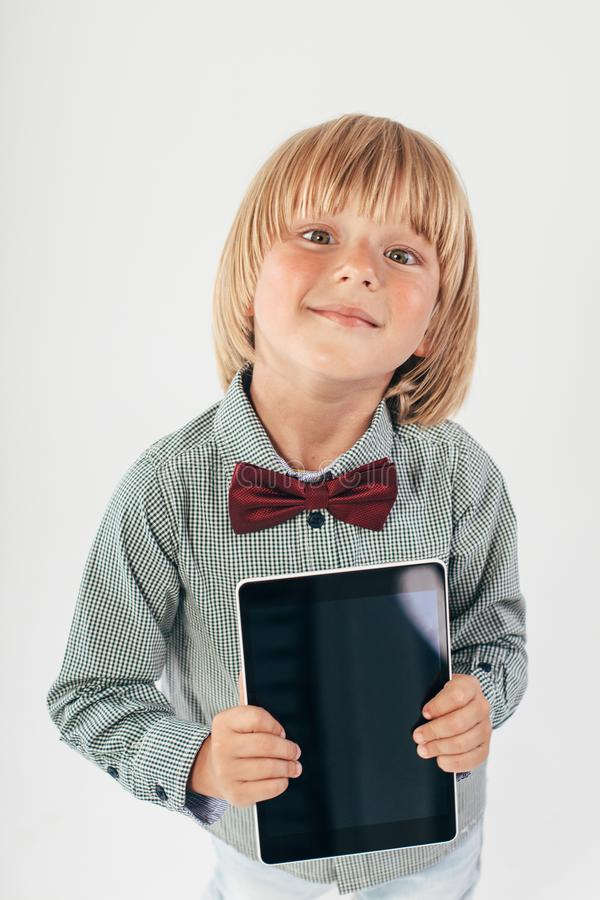 Smiling School boy in shirt with red bow tie, holding tablet computer and green apple in white background. Education, isolated. School preschool. Education royalty free stock images