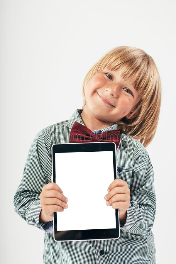 Smiling School boy in shirt with red bow tie, holding tablet computer and green apple in white background. Education, isolated. School preschool. Education stock image