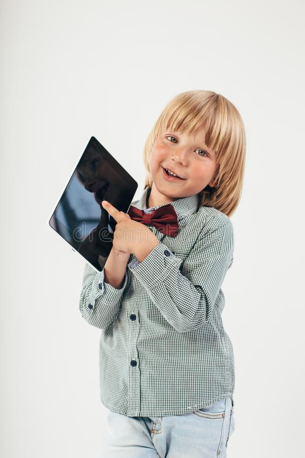 Smiling School boy in shirt with red bow tie, holding tablet computer and green apple in white background stock images