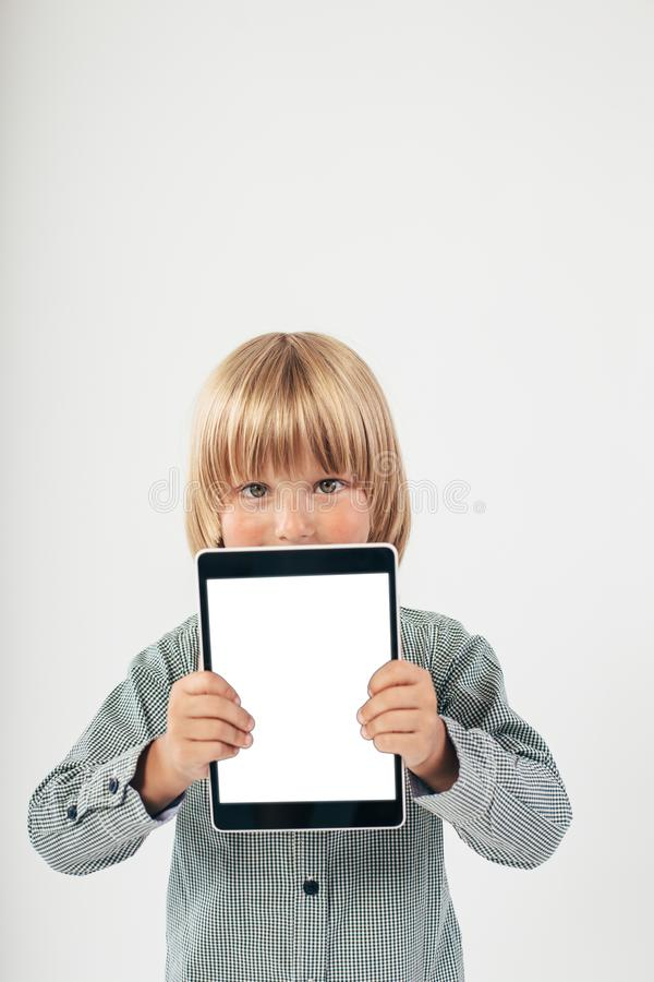 Smiling School boy in shirt with red bow tie, holding tablet computer in white background. Smart boy is a graduate. Schoolboy with glasses.Education, isolated royalty free stock photography