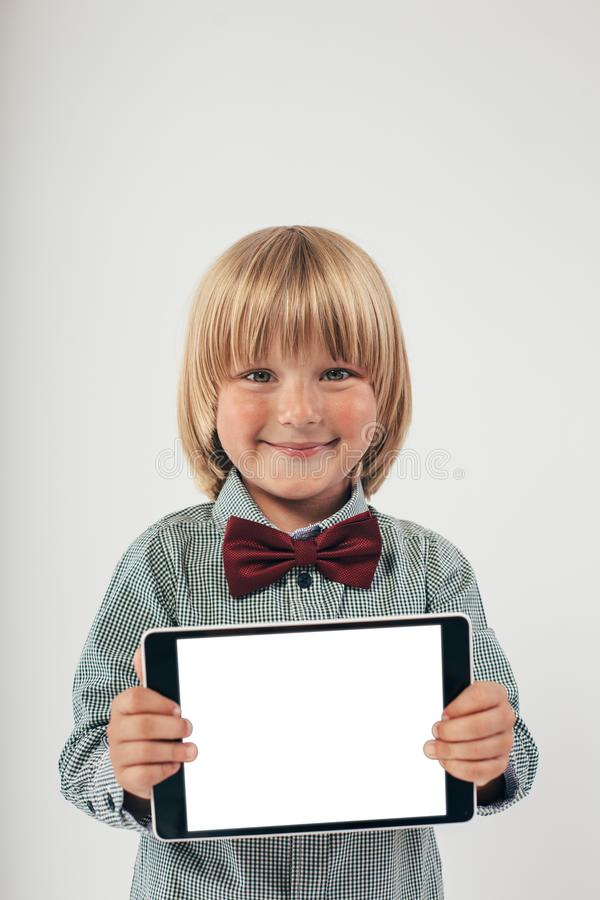 Smiling School boy in shirt with red bow tie, holding tablet computer in white background. Smart boy is a graduate. Schoolboy with glasses.Education, isolated royalty free stock images