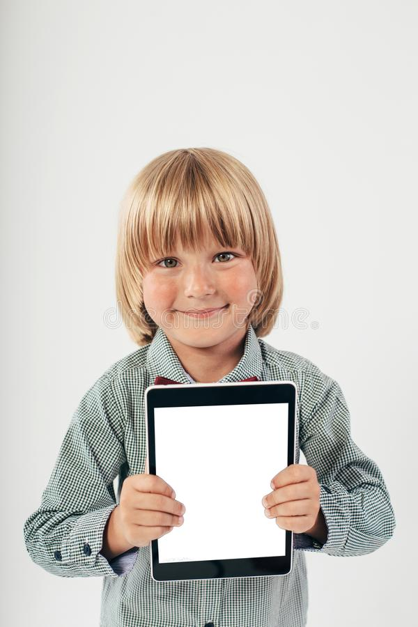 Smiling School boy in shirt with red bow tie, holding tablet computer in white background. Smart boy is a graduate. Schoolboy with glasses.Education, isolated stock photos