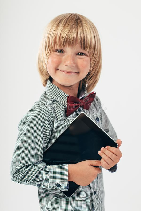 Smiling School boy in shirt with red bow tie, holding tablet computer in white background. Smart boy is a graduate. Schoolboy with glasses.Education, isolated stock image