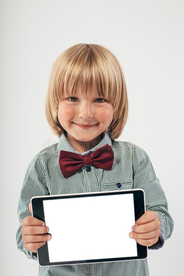 Smiling School boy in shirt with red bow tie, holding tablet computer in white background. Smart boy is a graduate. Schoolboy with glasses.Education, isolated stock photography