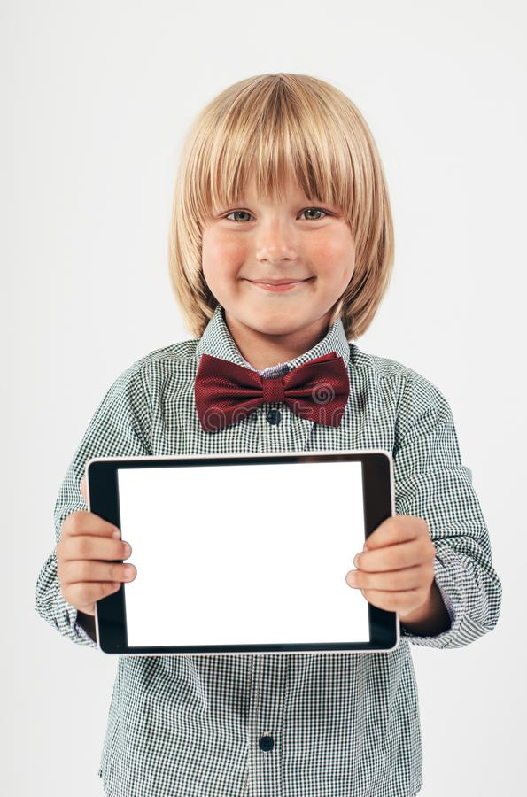 Smiling School boy in shirt with red bow tie, holding tablet computer in white background. Smart boy is a graduate. Schoolboy with glasses.Education, isolated stock images