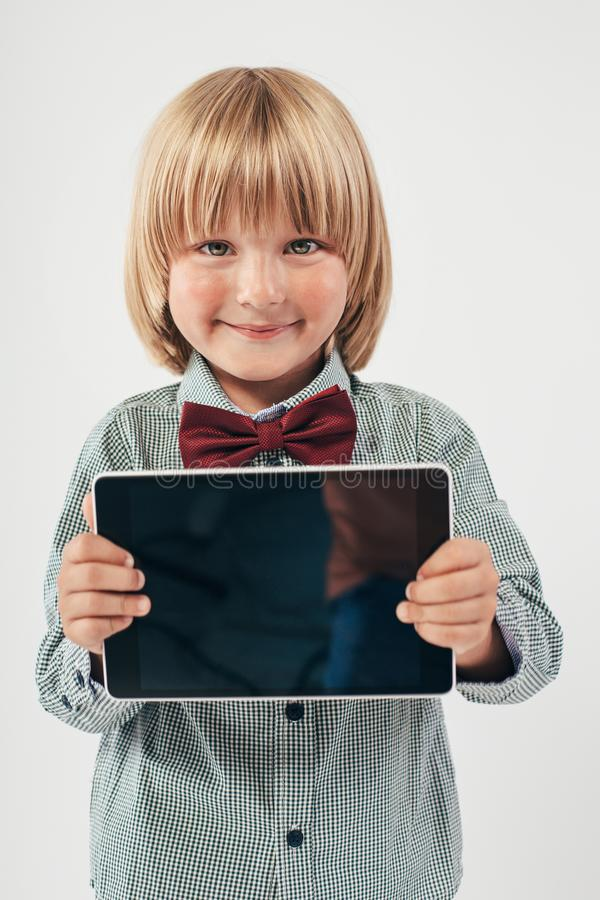 Smiling School boy in shirt with red bow tie, holding tablet computer in white background. Smart boy is a graduate. Schoolboy with glasses.Education, isolated royalty free stock photos