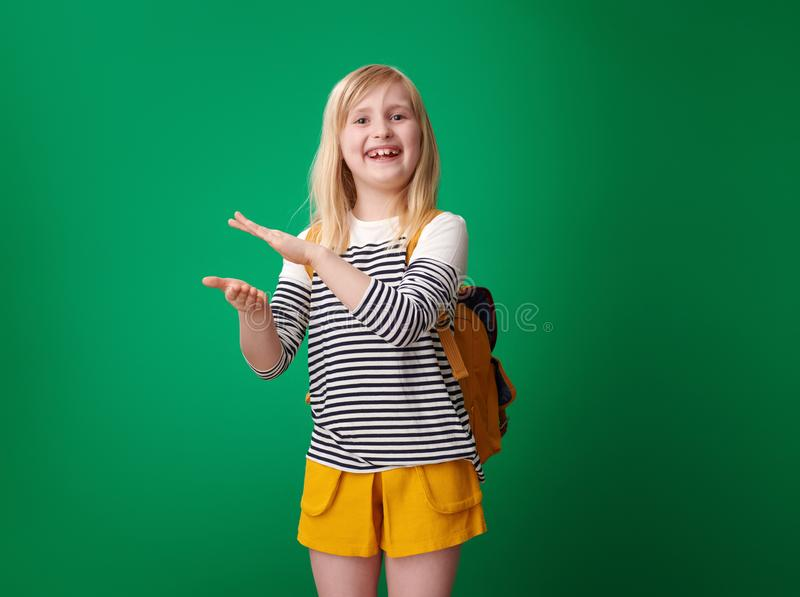 Smiling school girl clapping isolated on green background. Smiling school girl with backpack clapping isolated on green background royalty free stock photography