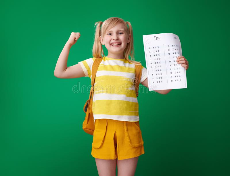 Smiling school girl with excellent grade test showing biceps. Smiling school girl with backpack with an excellent grade test showing biceps against green stock photography