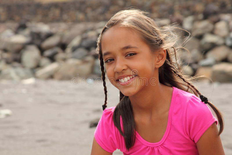 Smiling school girl in pink sitting on beach royalty free stock images