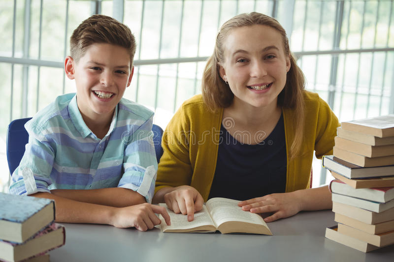 Smiling school kids reading books in library at school. Portrait of smiling school kids reading books in library at school royalty free stock photography